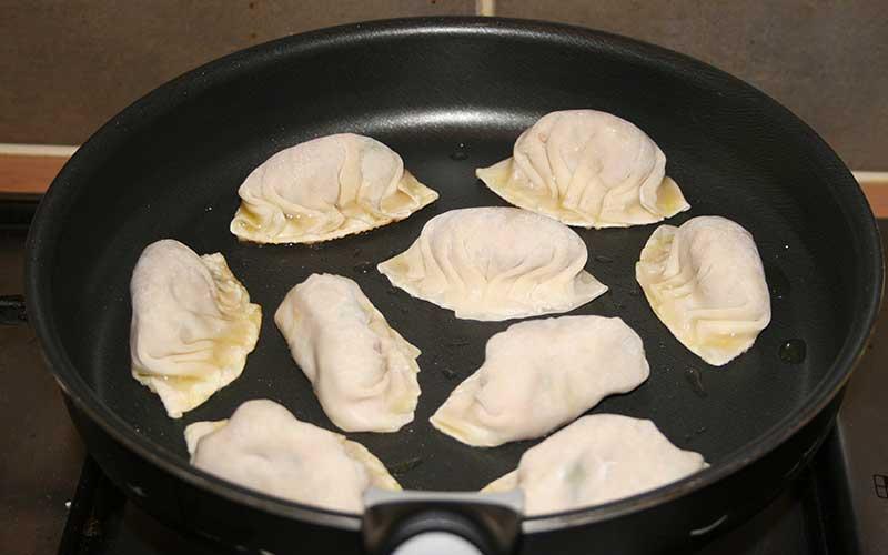 Verhit olie in een pan en leg de gyoza erin.
